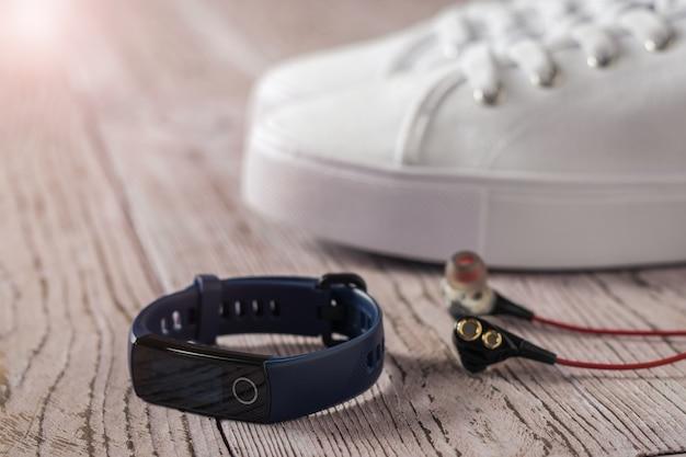 青いスマートブレスレット、白いスニーカー、木製のテーブルに赤いイヤホン。スポーツをコントロールするためのアクセサリー。スポーツスタイル。