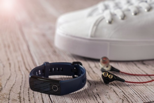 Blue smart bracelet, white sneakers and red earphones on wooden table. accessories to control sports. sports style.