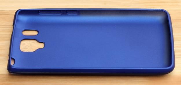 木製の背景に青いスマートフォンの裏表紙