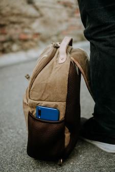 茶色の機能的なカメラバッグのサイドポケットに入れられた青いスマートフォン