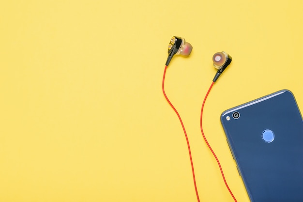 Blue smartphone with red headphones on yellow background.