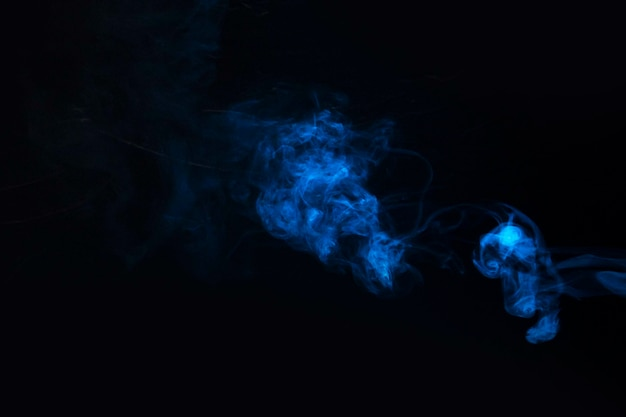 Blue smoke against black background