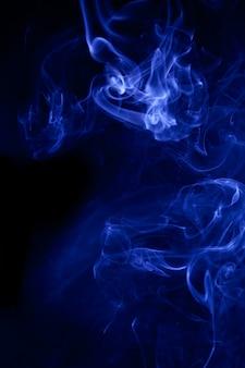 Blue smoke on a black background. Premium Photo