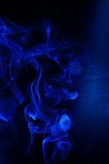 Движение синего дыма на черном фоне.