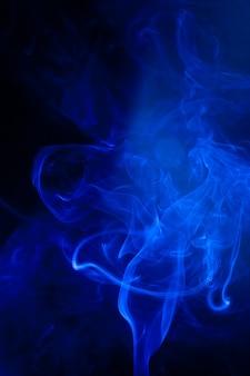 Движение синего дыма на черной поверхности.