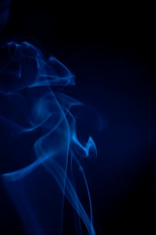 黒の背景に青い煙。