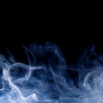 Blue smoke swirls over black background