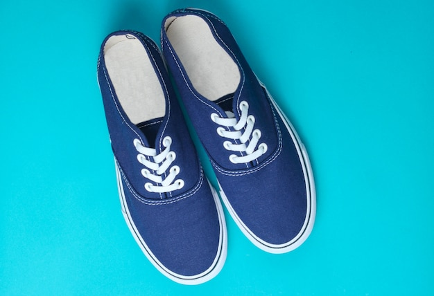 Blue sneakers on blue table. minimalism, fashion, top view