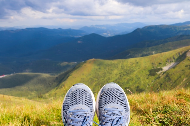 Blue sneakers of the traveler against the background of mountain landscapes tourism and travel