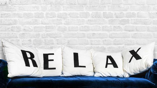 青いソファと白い枕にリラックスの文字が書かれています。白いヴィンテージのレンガの壁の背景のロフトスタイル。背景のモックアップをリラックスします。コピースペース