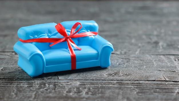 Синий диван, перевязанный красной подарочной лентой на черном деревянном полу. необычный подарок.