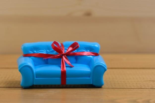 木製の背景に赤いギフトリボンで結ばれた青いソファ。珍しい贈り物。