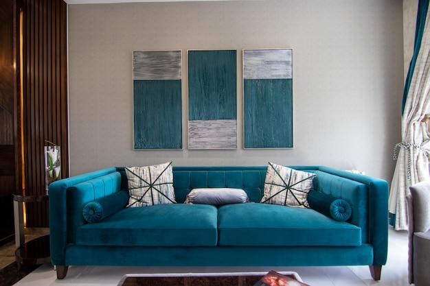 壁にフレームが付いている青いソファ