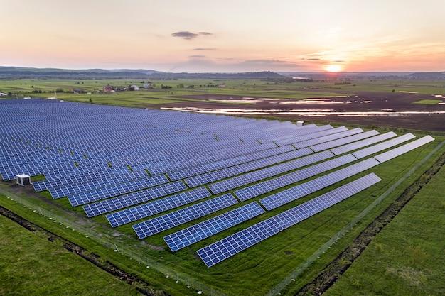 Голубая солнечная система фотоэлектрических панелей производит возобновляемую чистую энергию на фоне сельского пейзажа и заходящего солнца.