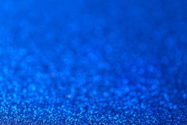 Blue sparkling background from small sequins, closeup, brilliant backdrop