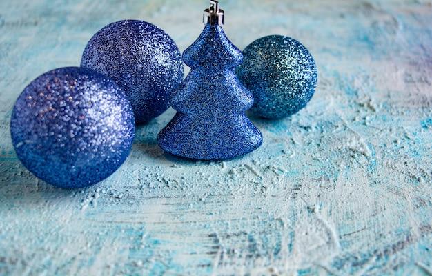 파란색 반짝이는 크리스마스 장식 공과 흰색과 파란색 배경 장식에 크리스마스 트리