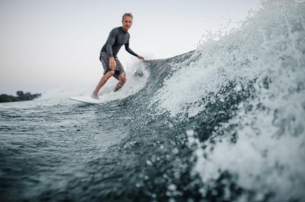 ダウンサーフィンをする男性と前景に焦点を当てた青いしぶき波