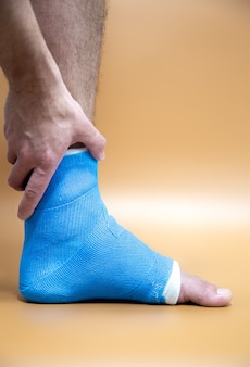 Blue splint ankle. bandaged leg cast on male patient on colored blurred background. sports injury concept.