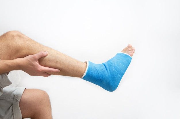 Blue splint ankle. bandaged leg cast on male patient on white background isolated. sports injury concept.