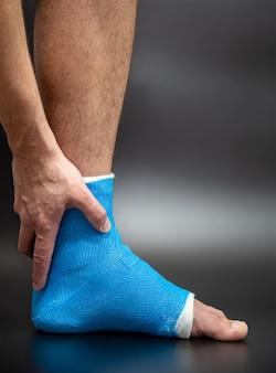 파란색 부목 발목. 어두운 배경을 흐리게에 남성 환자에 붕대 다리 캐스팅. 스포츠 부상 개념.