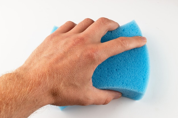 Blue sponge in hand on a white surface