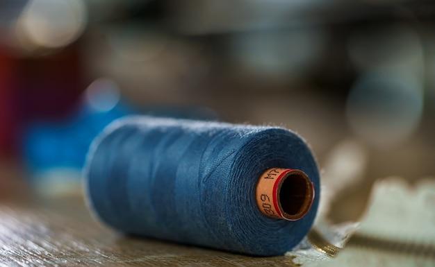 Синяя катушка на деревянном столе. концепция портного. концепция шитья.