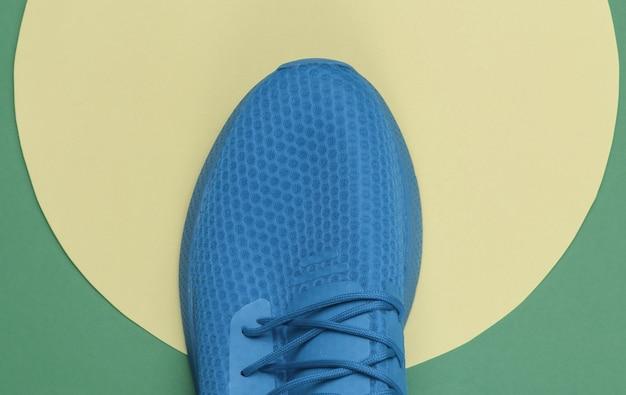 노란색 파스텔 원이 있는 파란색 스포츠 운동화 ongreen 배경입니다. 청소년 힙스터 개념입니다. 평면도