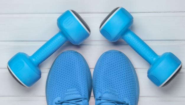 Синяя спортивная обувь для тренировок, гантели на белом деревянном полу. вид сверху.