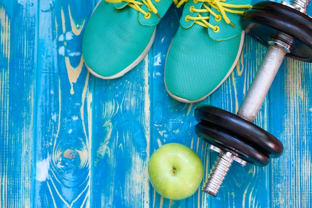 Blue sports sneakers with dumbbells, and a green apple