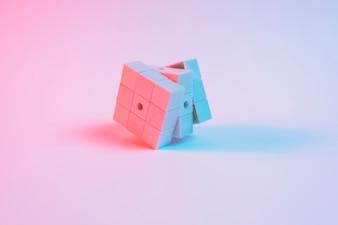 Голубое пятно света над кубиком розового рубика на простом фоне