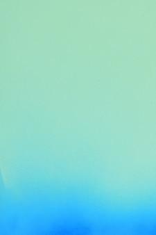 柔らかい緑色の紙の背景に青いスプレーペイント