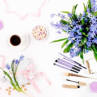 Голубой весенний букет, кофейная чашка, конфеты, подарок с розовой лентой и косметическими аксессуарами