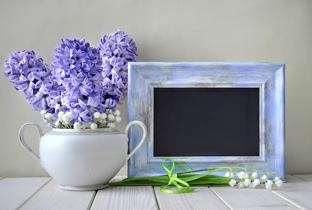 Blue springtime background. blue hyacinth  and lily of the valley flowers  with blackboard