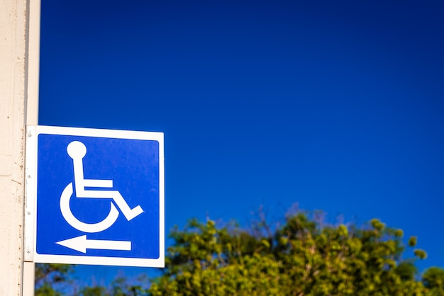 Blue square sign to indicate the way to disabled people in a wheelchair, copy space.