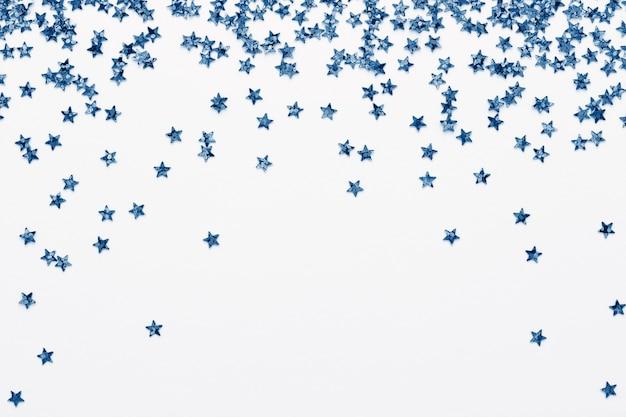 白いお祭りの背景に青い星紙吹雪