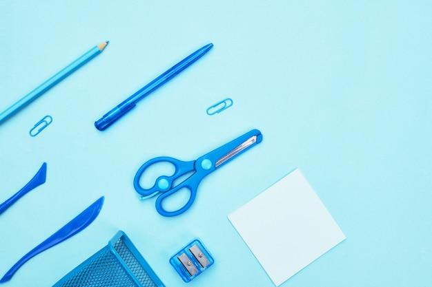 Синие канцелярские товары на синем фоне школа, copyspace