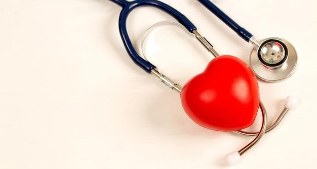 Синий стетоскоп и красное сердце на белом фоне, здоровье сердца
