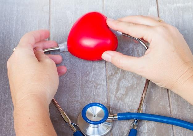 誰かの手と赤いハートの青い聴診器