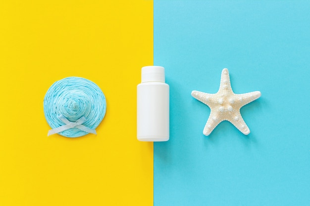 Blue straw hat, starfish and white tube, bottle of sunscreen on yellow and blue paper background
