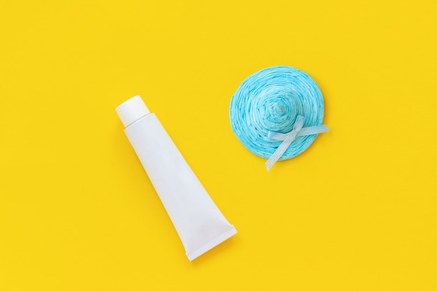 Blue straw hat and white tube of sunscreen on yellow paper background