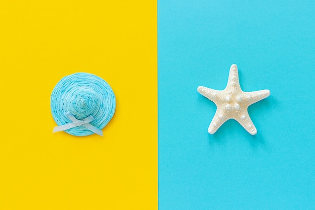 Blue straw hat on yellow paper and sea starfish on blue background
