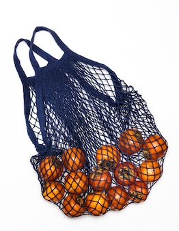 Blue string bag with persimmons on a white background