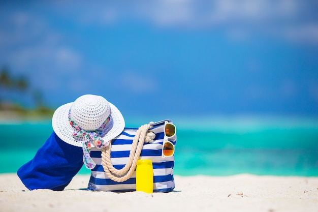 Blue stripe bag and towel, straw white hat, sunglasses, sunscreen bottle on exotic beach