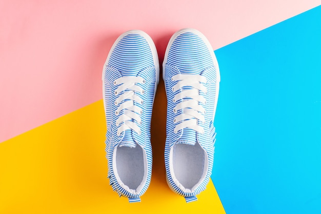 Blue striped female sneakers on a colorful background top view. flat lay minimal background