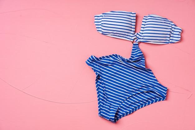 Blue striped monokini on pink, flat lay