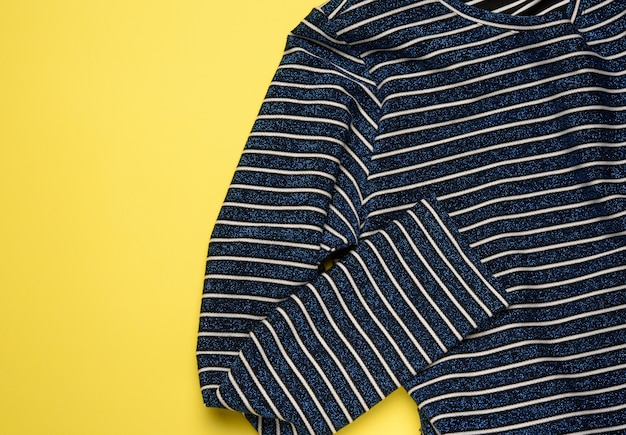 Blue striped textile women's pullover on a yellow background, top view