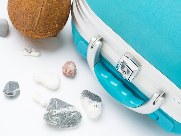 Blue suitcase, coconut and sea stones. exotic destinations travel concept