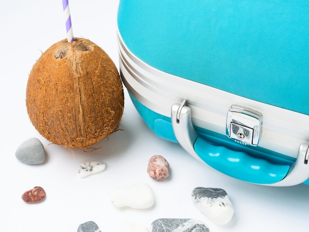 Blue suitcase, coconut and sea stones