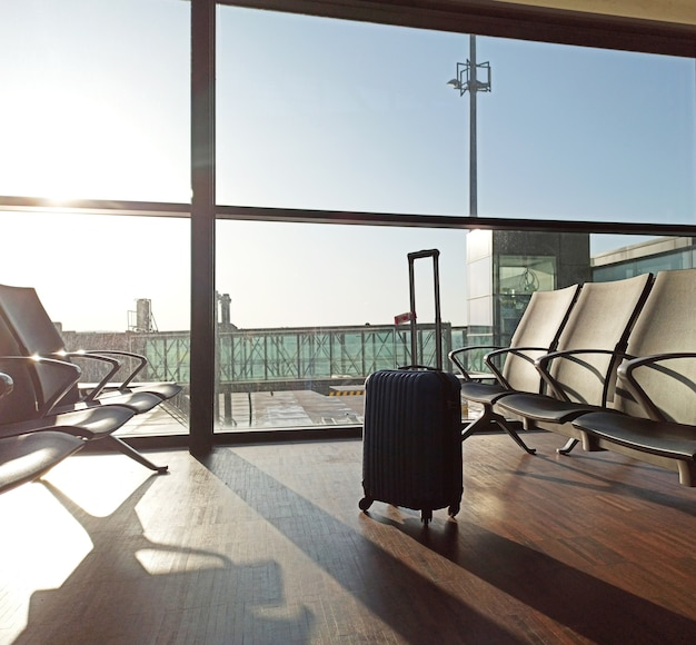 Синий чемодан в пустом аэропорту. зона ожидания отмена задержки рейса. путешествие и отдых