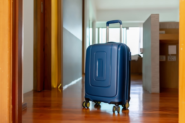 Blue suitcase in light hotel room with brown wooden details. copy space